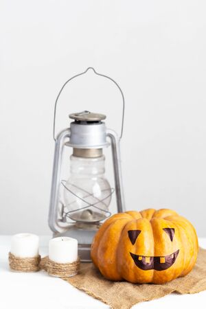 scary face pumpkin, candles and lantern on a white wooden table. Autumn Halloween concept.