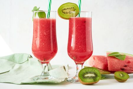 Two glasses of fresh watermelon smoothie with kiwi and mint on a white wooden table Stock fotó