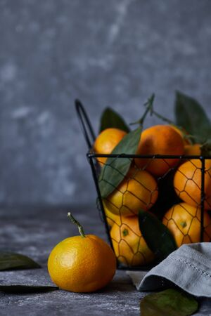 fresh tangerines with leaves in a basket on a dark background Copy space