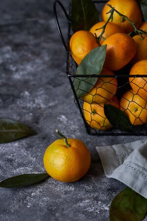 Tasty tangerines with leaves in a basket on a dark background Close up Vertical 스톡 콘텐츠