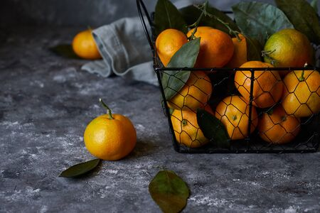 Tasty tangerines with leaves in a basket on a dark background Copy space 스톡 콘텐츠 - 130024475