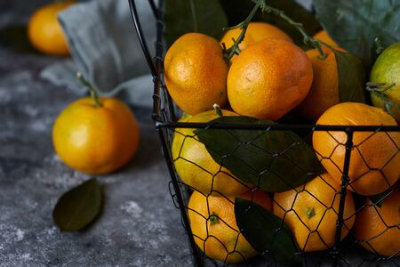 fresh tangerines with leaves in a basket on a dark background Close up 스톡 콘텐츠 - 130024476