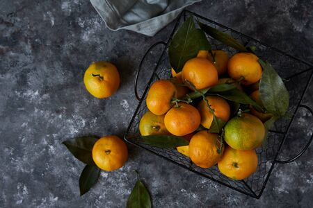 Juicy tangerines with leaves in a basket on a dark background Copy space Top view 免版税图像