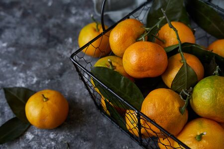 fresh tangerines with leaves in a basket on a dark background Copy space Top view 스톡 콘텐츠