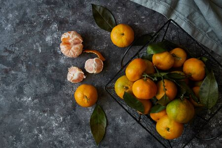 fresh tangerines with leaves in a basket on a dark background Copy space Top view 스톡 콘텐츠 - 130024483