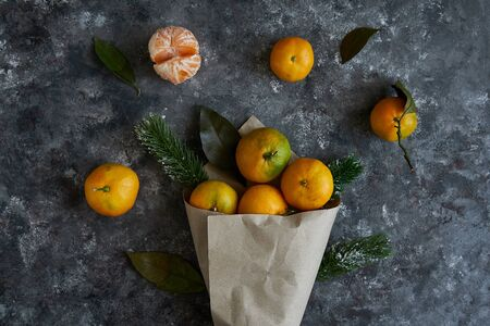 Juicy tangerines with leaves and fir branches in a paper bag on a dark background New Year concept 스톡 콘텐츠