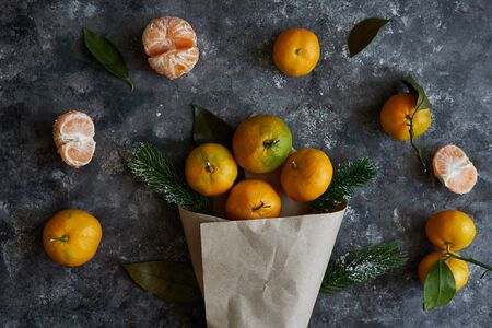 Fresh tangerines with leaves and fir branches in a paper bag on a dark background New Year concept