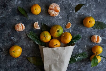 Tasty tangerines with leaves and fir branches in a paper bag on a dark background New Year concept