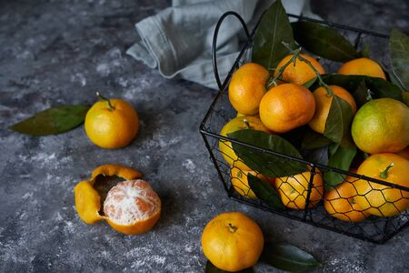 Juicy tangerines with leaves in a basket on a dark background Copy space Top view 스톡 콘텐츠