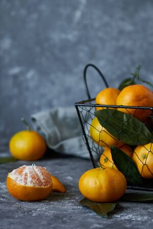 Juicy tangerines with leaves in a basket on a dark background Copy space Vertical 스톡 콘텐츠