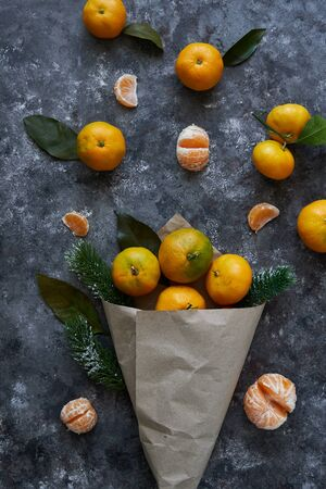 Juicy tangerines with leaves and fir branches in a paper bag on a dark background New Year concept 스톡 콘텐츠 - 130024505
