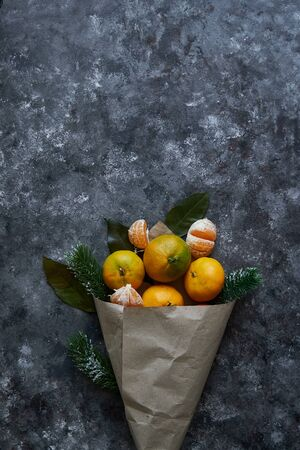 Juicy tangerines with leaves and fir branches in a paper bag on a dark background New Year Christmas concept