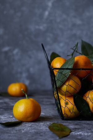 fresh tangerines with leaves in a basket on a dark background Close up 스톡 콘텐츠