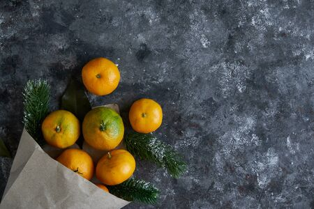 Tasty tangerines with leaves and fir branches in a paper bag on a dark background New Year Chrismas concept