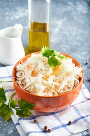 Sauerkraut with seasonings in an orange bowl. Natural Probiotics, Healthy Food Close up