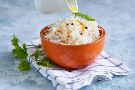 Cook sprinkles olive oil on sauerkraut in a bowl. Healthy probiotic food Close up
