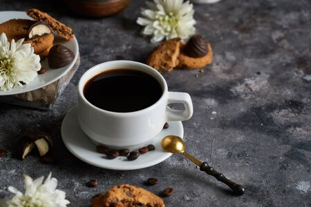 White cup of black strong coffee with coffee beans and cookies on dark background