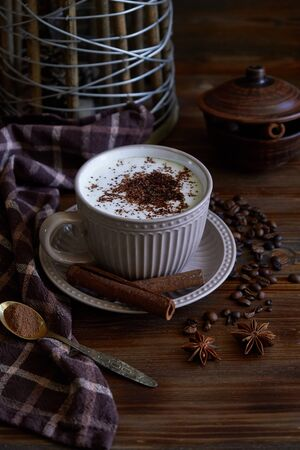 Cup of capuccino coffee with cinnamon and coffee beans on wooden background Vertical Stockfoto
