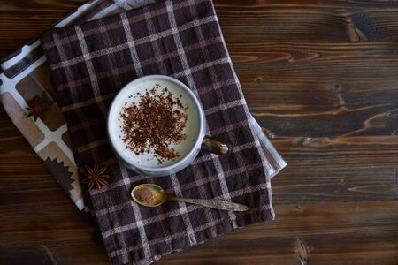 Cup of capuccino coffee with cinnamon and coffee beans on wooden background Copy space Top view