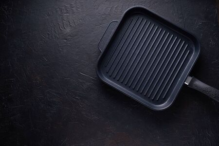 Grill pan on dark stone background Copy space Top view Reklamní fotografie