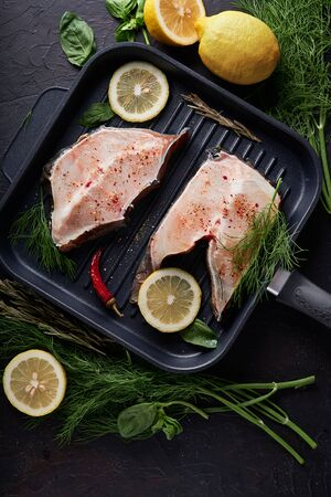 fresh fillet of sea fish in a grill pan Copy space On dark background Vertical 스톡 콘텐츠