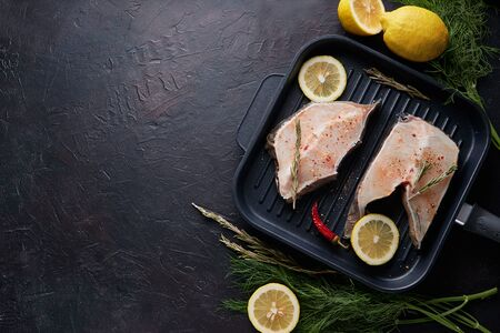 fresh fillet of sea fish in a grill pan Copy space On dark background Фото со стока