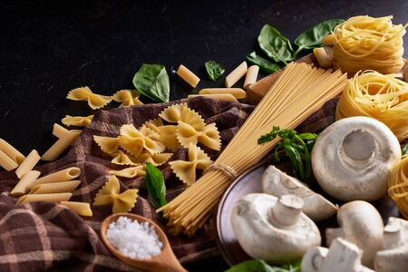 ingredients for cooking traditional pasta with mushrooms on dark stone background.