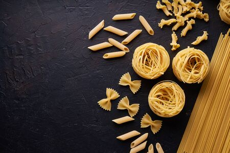 assortment of pasta for cooking on dark stone background Copy space
