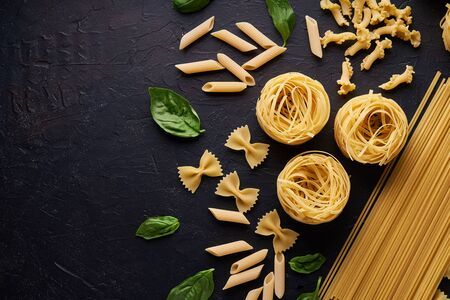 assortment of pasta with green leaf on dark stone background Copy space Stock fotó - 133400886