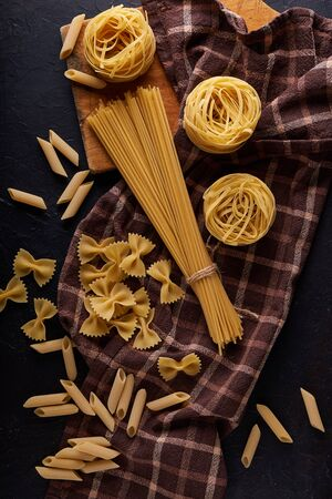 assortment of pasta on dark stone background Copy space Vertical 스톡 콘텐츠