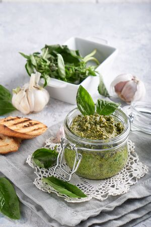 traditional italian basil pesto sauce in a glass jar wiht toasts on a light stone table Vertical