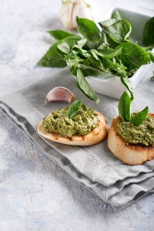 Toasts with traditional Italian basil pesto sauce on a light stone table Vertical 스톡 콘텐츠