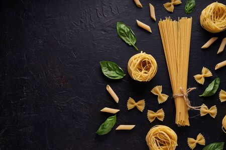 assortment of pasta with green leaf on dark stone background Copy space Stock fotó