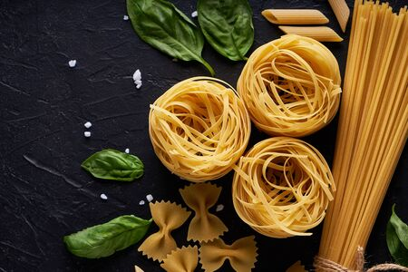assortment of pasta with green leaf on dark stone background Copy space 스톡 콘텐츠