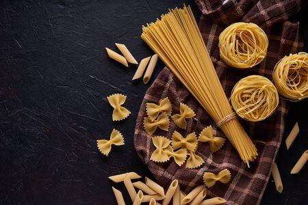 assortment of pasta on dark stone background Copy space Stock fotó - 133400889