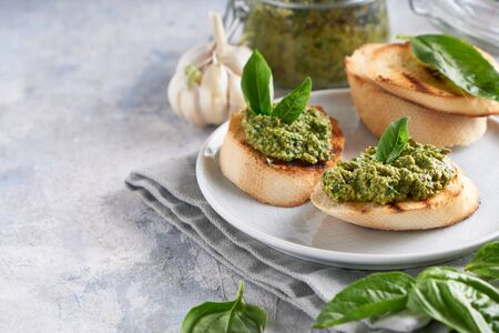 Toasts with traditional Italian basil pesto sauce on a light stone table Copyspace