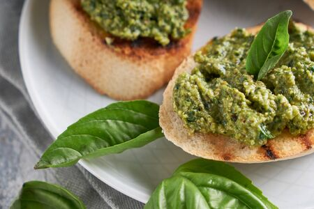Toasts with traditional Italian basil pesto sauce on a light stone table Close up Stock fotó - 133400896