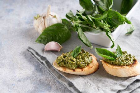 Toasts with traditional Italian basil pesto sauce on a light stone table Copy space