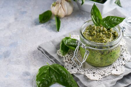 traditional italian basil pesto sauce in a glass jar on a light stone table Copyspace