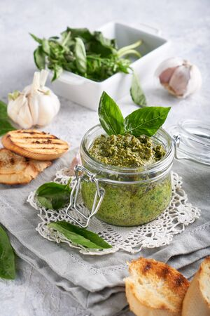 traditional italian basil pesto sauce in a glass jar wiht toasts on a light stone table Vertical Stock fotó - 133400888