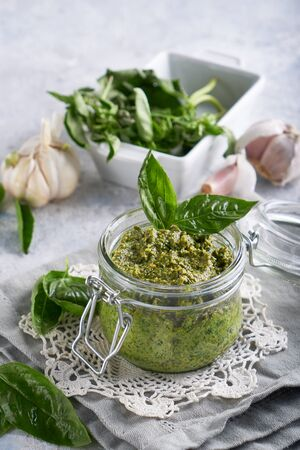 traditional italian basil pesto sauce in a glass jar on a light stone table Vertical Copy space
