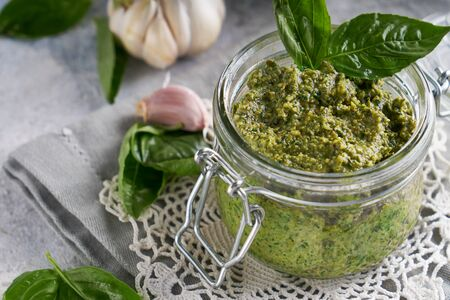 traditional italian basil pesto sauce in a glass jar on a light stone table Close-up