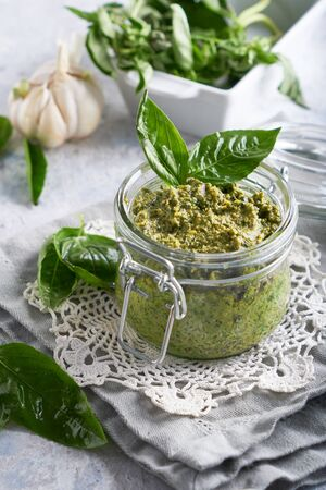 traditional italian basil pesto sauce in a glass jar on a light stone table Vertical 스톡 콘텐츠
