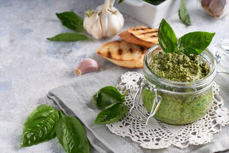 traditional italian basil pesto sauce in a glass jar wiht toasts on a light stone table Copy space