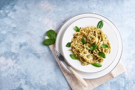 Appetizing pasta with sauce pesto and spinach in plate on light blue stone table Top view Copy space