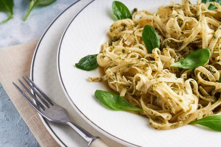Appetizing pasta with sauce pesto and spinach in plate on light blue stone table