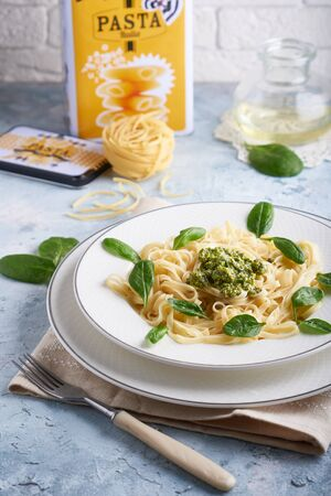 Appetizing pasta with sauce pesto and spinach in plate on light blue stone table Vertical