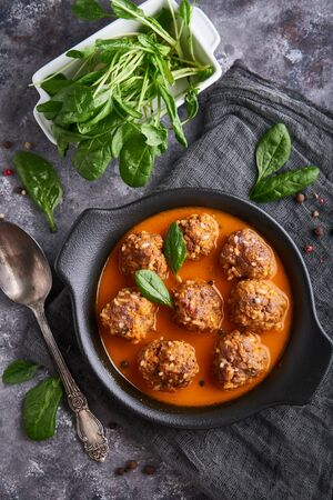 homemade meatballs with tomato sauce and spinach in a plate on a dark background