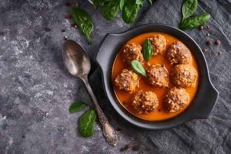 Appetizing homemade meatballs with tomato sauce and spinach served in a plate on a dark stone table Copy space Top view