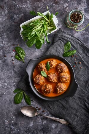homemade meatballs with tomato sauce and spinach served in a plate on a dark stone table
